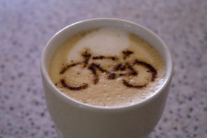 Cup of coffee with a bicycle image dusted on top